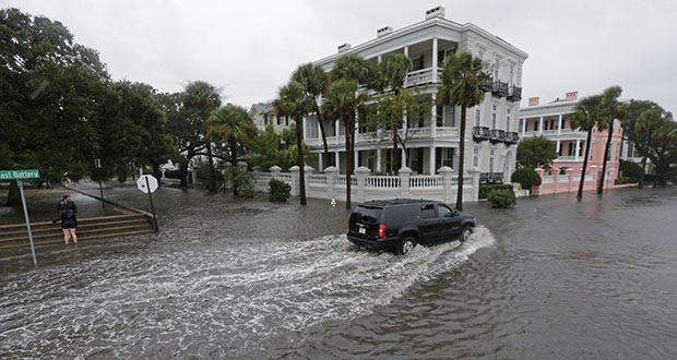In this Oct. 3, 2015, photo, a driver takes his truck through a flooded street in Charleston, South Carolina. Historic coastal cities in the Southeast U.S. have survived disease outbreaks, wars and hurricanes over the past three centuries. Now they are trying to figure how to survive rising seas from climate change. (AP file photo)