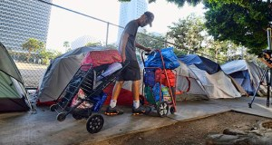 A homeless man moves his belongings from a street near Los Angeles City Hall, background, as crews prepared to clean the area on July 1. (AP file photo)