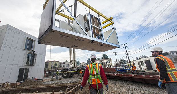 Contractors swing a Nemo Building Systems modular housing unit into place during installation in 2016 at the University of California, Berkeley. (Bloomberg file photo)