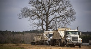Trucks sit parked in a line Dec. 9 at a construction site outside of Center, Texas. The site, which is in an opportunity zone, will be the home of a new feeding mill for chickens for Tyson Foods. (Bloomberg photo: Sergio Flores)