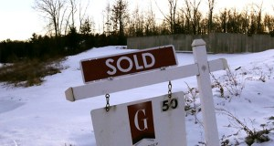 In this Jan. 9, 2020, photo a sold sign is posted on a real estate sign in front of the foundation of a pre-constructed home in Derry, N.H. (AP Photo/Charles Krupa)