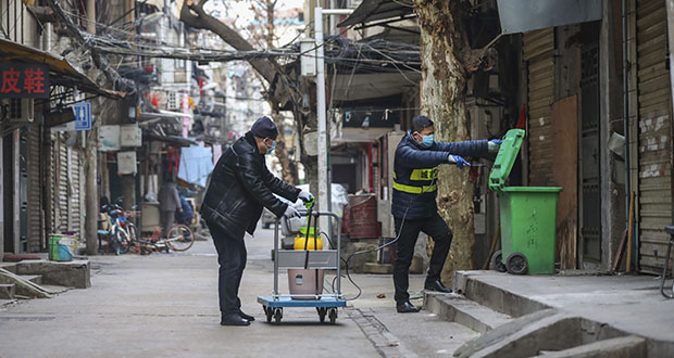 Government workers spray disinfectant on a garbage can Tuesday in Wuhan in central China's Hubei Province. Hong Kong's leader announced Tuesday that all rail links to mainland China will be cut starting Friday as fears grow about the spread of a new virus. (Photo: Chinatopix via AP)