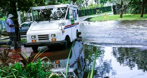 In this June 19, 2019 photo, a postal worker returns to their truck parked on a flooded street in Miami caused by high tides. Florida lawmakers advanced a proposal Tuesday that would create a statewide Office of Resiliency and establish a task force look into how best to protect the state's coastline from rising oceans. (AP file photo)