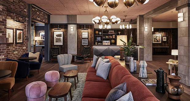 This photo shows the lobby in The Hoxton Hotel in Portland, Oregon, designed by London/L.A.-based Fettle. Alongside newly built rooms, public areas were situated in an old converted movie theater. Tailored but comfy mohair and leather seating and warm wood side tables blend with distressed rugs and displays of ceramics, plants and books. Refurbished timber and concrete beams frame the spaces. (Photo: Ennismore/The Hoxton via AP)