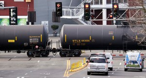 In this Feb. 13, 2018, file photo, automobile traffic waits at a train crossing as train cars that carry oil are pulled through downtown Seattle. (AP Photo/Elaine Thompson, File)