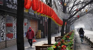 A woman walks past Lunar New Year decorations and shuttered bars Feb. 11 in a Beijing retail district. Millions of Chinese workers and entrepreneurs are bearing the rising costs of an anti-virus campaign that has shut down large sections of the economy. (AP photo: Ng Han Guan)