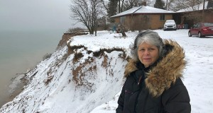 Rita Alton stands next to her house Jan. 14 on the edge of a cliff overlooking Lake Michigan near Manistee, Michigan. When her father built the 1,000-square-foot, brick bungalow in the early 1950s, more than acre of land lay between it and the drop-off overlooking the water. But erosion has accelerated dramatically as the lake approaches its highest levels in recorded history, hurling powerful waves into the mostly clay bluff. (AP Photo: John Flesher)