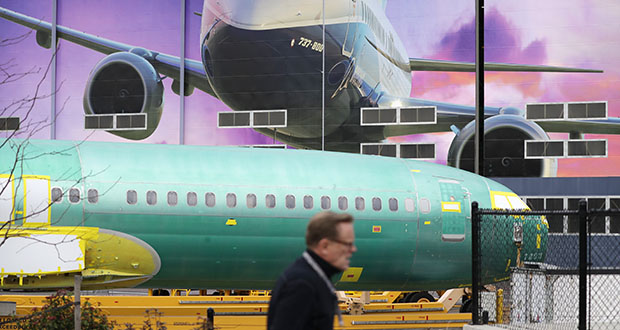 Boeing's decision to halt production of the 737 MAX aircraft slowed U.S. industrial production in January. In this Dec. 16, 2019, photo a Boeing worker walks past a 737 model fuselage and a giant mural of a jet on the side of the manufacturing building behind in Renton, Washington. (AP file photo)