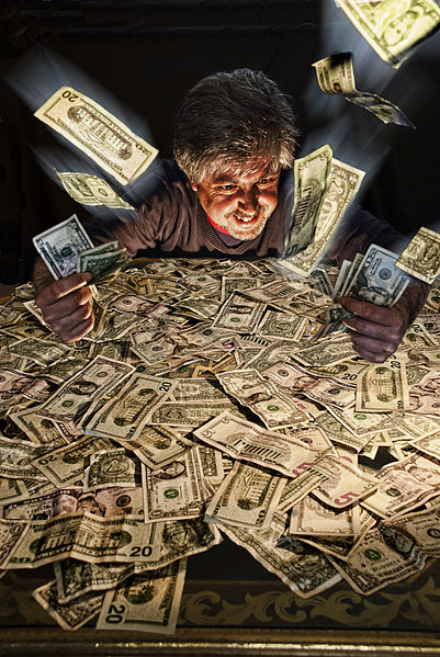 Image of a man wallowing in lots of cash; portraying 'Is it greed to seek wealth'