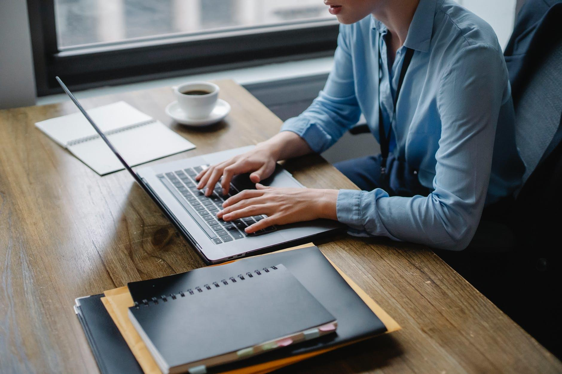 person in blue long sleeve shirt using macbook pro on brown wooden table
