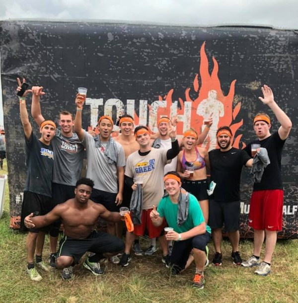 Group of us posing in front of the tough mudder finisher sign