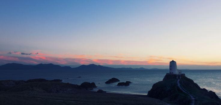 Financial Glass - Sunrise over an ocean lighthouse