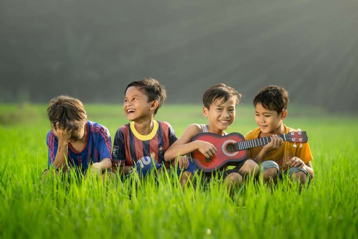 kids playing a guitar and laughing