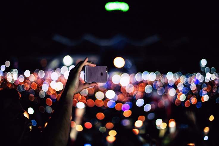 Hand holding phone above crowd at a concert
