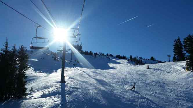 ski run with sun glare and blue skies
