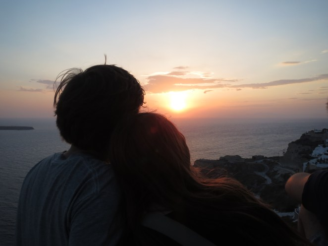 silhouette of two people watching sunset