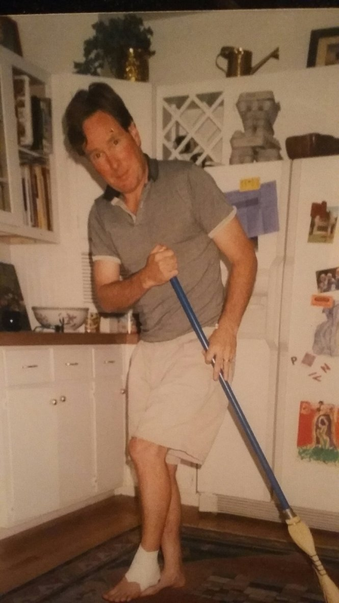 Dad with a broom in the kitchen