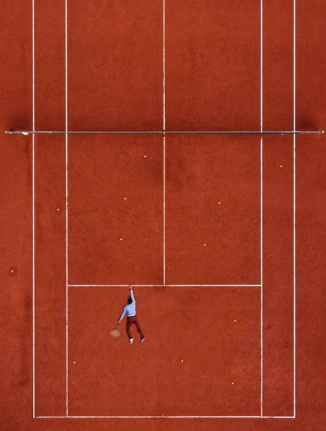 A flipped tennis court, the player hanging on for dear life