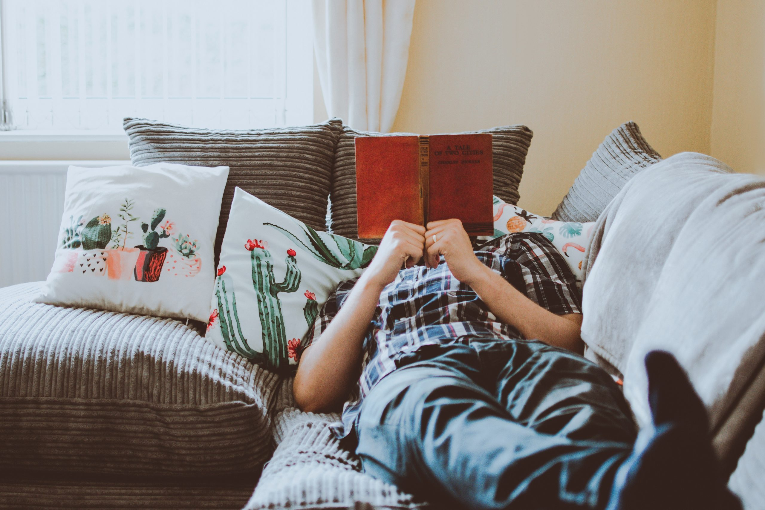 person-laying-on-sofa-while-reading-book-1471991.jpg