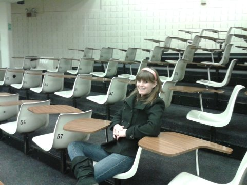 Woman sitting in empty lecture hall
