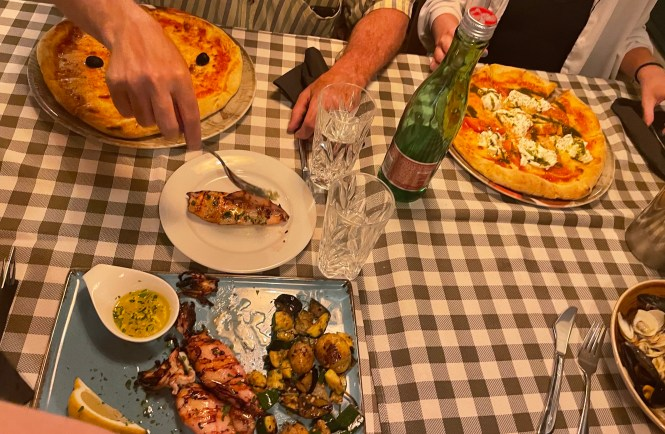 four entrees on a table with pizza and grilled squid