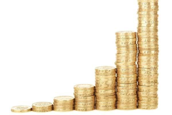 Stacks of coins of increasing proportion representing the benefits of investing in retirement early as a young professional