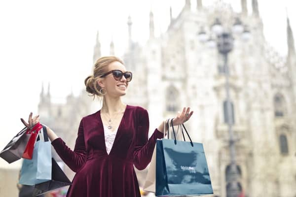woman carrying several shopping bags after paying herself first
