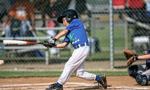 A kid hitting a baseball playing for a club baseball team
