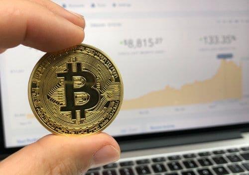 Mężczyzna trzyma w dłoni monetę bitcoin