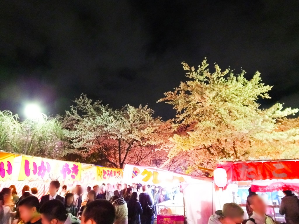 food stalls and lots of people under cherry trees