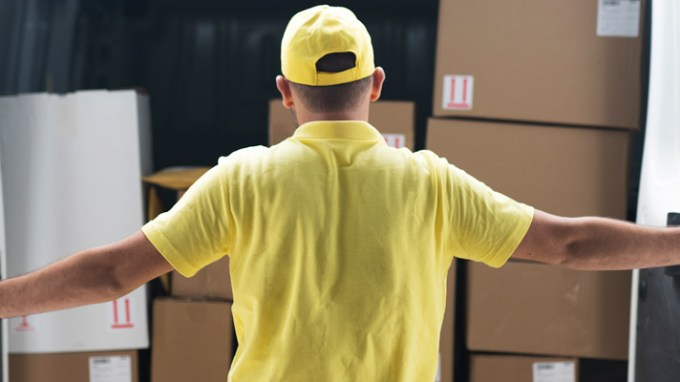 a small business worker opening the back door of delivery truck