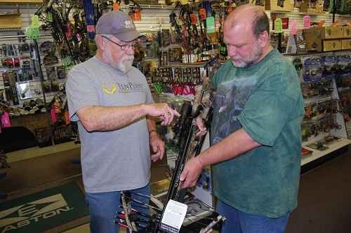 Man Showing Another Man Crossbow