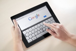 Kiev, Ukraine - December 03, 2011: Woman hands holding and touching on Apple iPad2 with Google search web page on a screen.