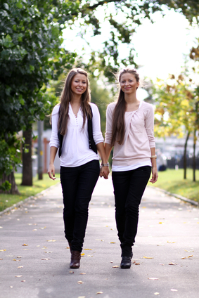 Fashionable girls twins walk in the street