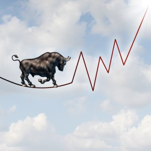 Bull market risk financial concept as a heavy bullish beast walking on a high tightrope shaped as a stock market profit chart representing the investment danger ahead.