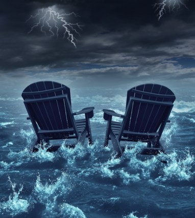 Retirement crisis concept as a couple of adirondack chairs sinking in the ocean during a thunder storm as a metaphor for financial investment problems for retiring seniors who lost their savings or broken dreams symbol.