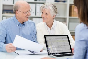 Elderly couple in a meeting with an adviser discussing a document as she watches across the desk in her office