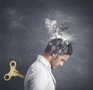 Concept of stress with gear in the head of a businessman