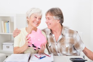 Portrait Of Smiling Senior Couple Saving Money In The Pink Piggybank