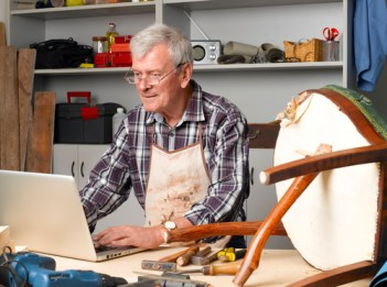 Portrait of retired manual worker sittiing in his small workshop in front of laptop and making online order. Small business.