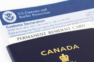 Close up of Canadian passport, permanent resident card, and customs declaration form, some of the paper work required for each entry into the United States.