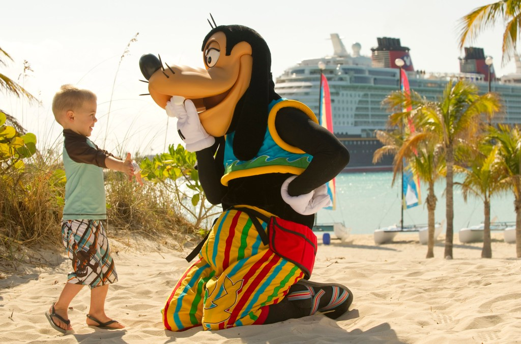 Goofy laughs with a child on the beach at Castaway Cay. Disney Cruise Line offers Military Discounts on Disney Vacations.