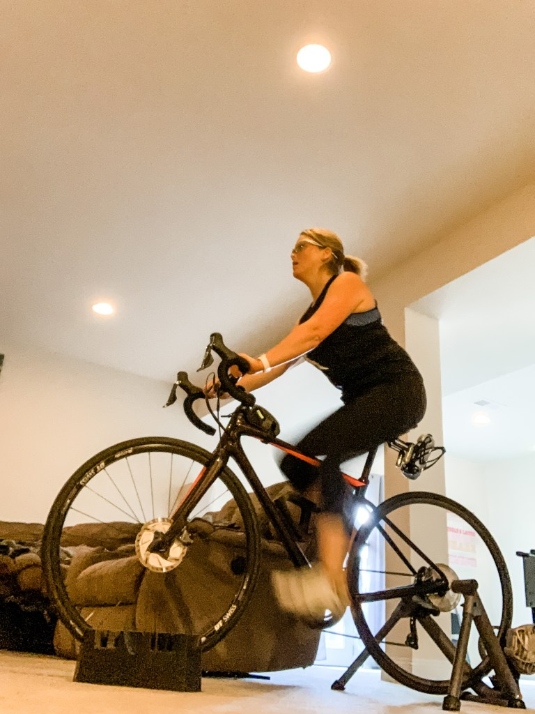 Woman rides a carbon road bike in her living room as a peloton alternative