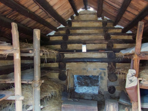 Interior of log cabin soldiers' huts at Valley Forge with fireplace in the rear.