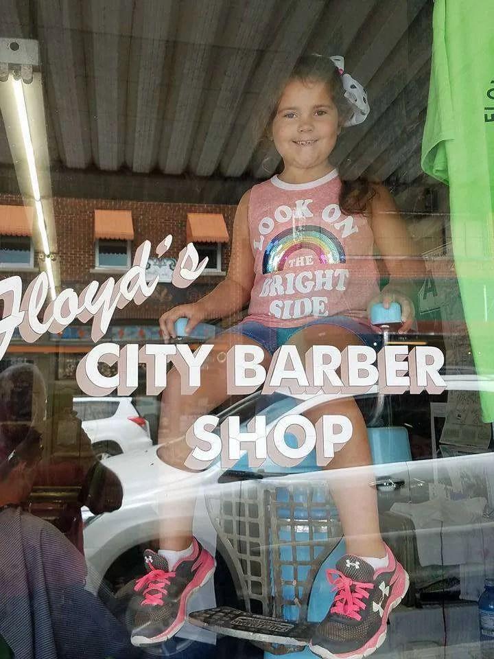 Girls sitting in window at Floyd's Barber Shop