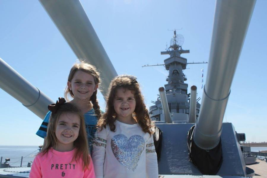 girls in front of USS Alabama mast and guns