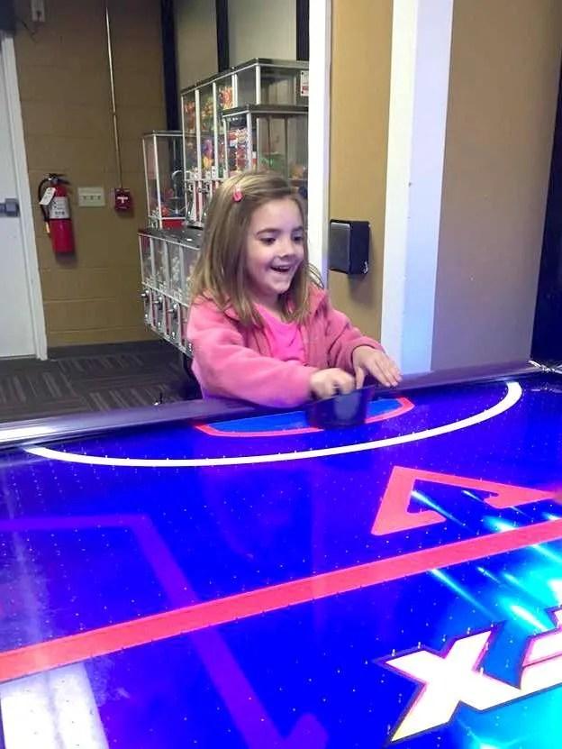 girl playing air hockey at arcade at Shenandoah Crossing Lodge