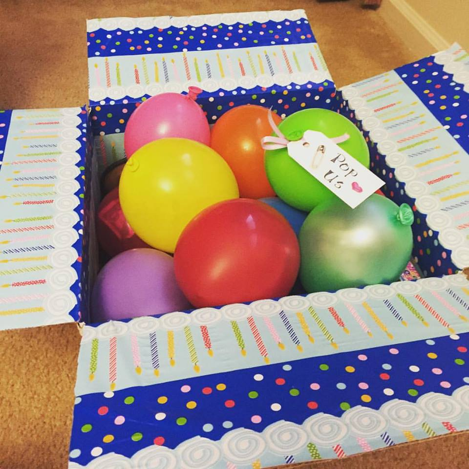 kids birthday care package with balloons filled with money and toys that say 'Pop Us'