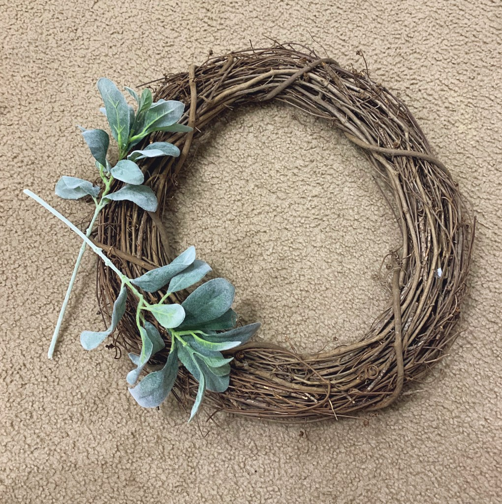 Step 3: Attach greenery to the wreath.