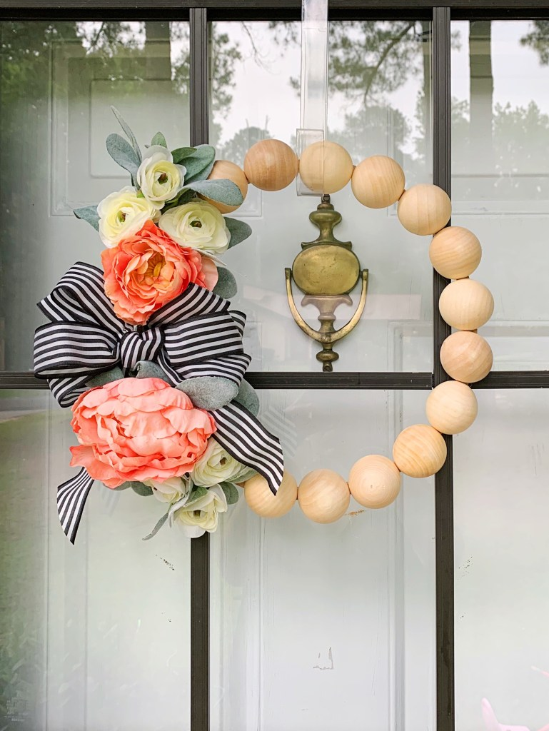 The final step to this DIY wood bead wreath is to add a bow!
